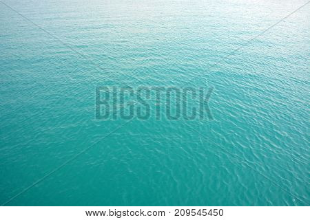 Blue natural sea water color background, waves and glare