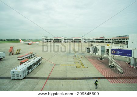 BANGKOK THAILAND  21 JULY 2017: Ground crew directing an incoming airplane into position to meet a jet-way bridge in Don Mueang international airport (DMK)