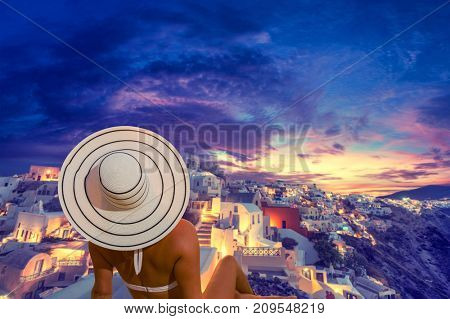 Woman with hat watching Oia village on santorini island in Greece at sunset