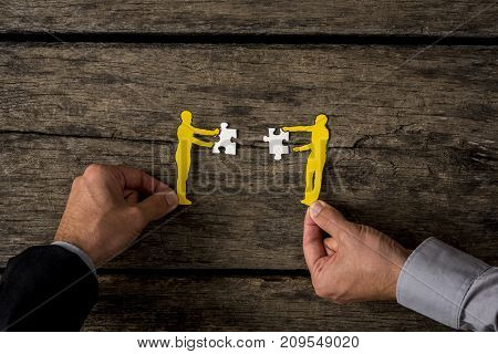 Two businessmen using paper cutout silhouettes of men holding puzzle pieces on rustic wood.