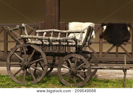 Traditional Caucasian cart before the porch railing with the animal skins laid on them