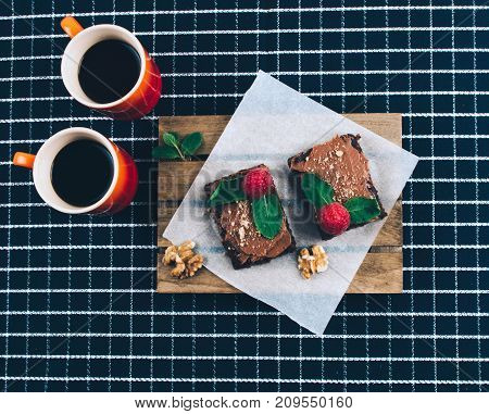 Cup of coffee with homemade vegan cake brownies. Flat lay style