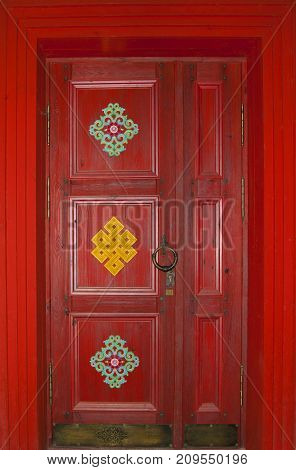 scarlet wooden door in Buryat or Tibetan style (in Buddhist datsan - monastery) with a bronze handle-ring and national patterns in full frame