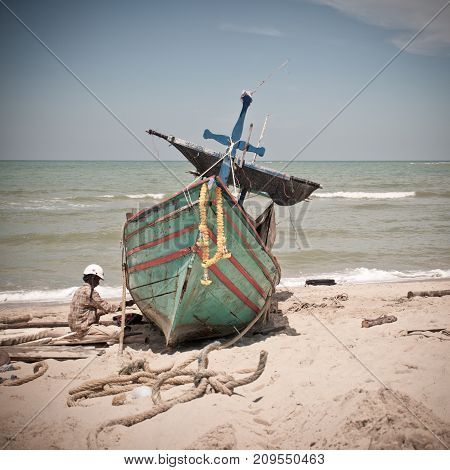 Samila Beach Songkhla Thailand - March 23 2017: Fishermen are repairing fishing boat on Samila beach.