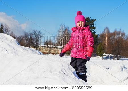 Joyful girl on a walk in winter's day. She stands on top of a mountain