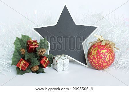 An empty slate in the shape of a star to write a message with red and white gifts, green leaves, a fir tree crown and a red ball, a frosted white  garland on a white background