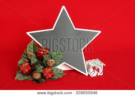 An empty slate in the form of a star to write a message on a red background with red and white gifts placed on a wreath of fir for decoration of fetes