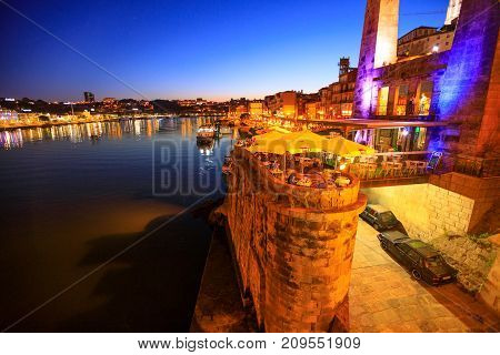 Porto, Portugal - August 10, 2017: Nightlife in Porto: bars, clubs and restaurants at Ribeira waterfront illuminated by night. Scenic view from Dom Luis I Bridge on Douro River and urban skyline.