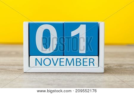 November 1st. Day 1 of month, wooden color calendar on yellow background. Autumn time.