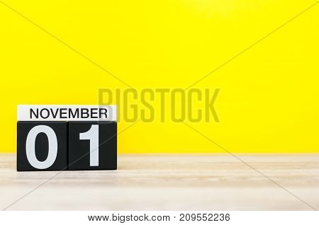 November 1st. Day 1 of month, wooden color calendar on yellow background. Autumn time. Empty space for text.