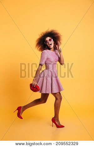 Full length portrait of an attractive cheerful afro american woman in retro style clothes holding purse while standing and posing isolated over yellow background