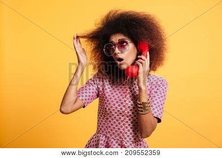 Portrait of a surprised afro american woman in retro style clothes talking on telephone isolated over yellow background