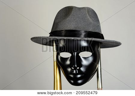 Black theater mask and hat hanging on a brass pipe on gray background with copy space. Social masking and mystery concept