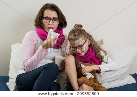 Sick mother and daughter. A woman with a runny nose she sneezes using a handkerchief drinking hot tea medicine.