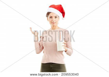 Portrait of woman in Santa hat holding bottle of milk on white background