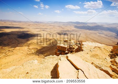 The bottom of Ramon Crater (Makhtesh Ramon), the largest in the world, as seen from the high rocky cliff edge surrounding it from the north, Ramon Nature reserve, Mitzpe Ramon, Negev desert, Israel