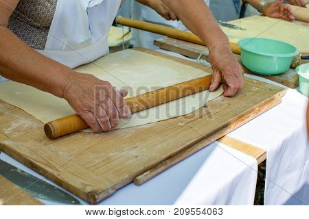 Old wrinkled hands of elderly woman rolling out dough with rolling pin on a wooden cutting board. Concept - benefits of cooking at home, active life in old age.