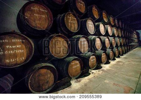 Porto, Portugal - August 13, 2017: Row of wooden porto wine barrels in wine cellar in Ferreira winery, Vila Nova de Gaia on Douro River, one of the most popular wine tasting tours.