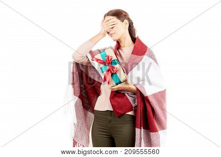 Portrait of woman wrapped in blanket holding Christmas gift