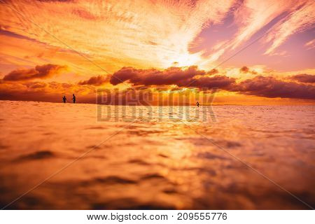 Stand up paddle board, quiet sea with warm sunset or sunrise colors. Relaxing on ocean