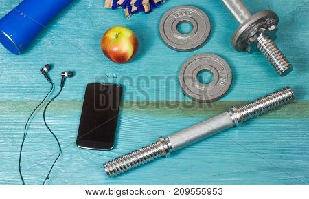 Weight plates, gloves and smartphone on wooden background, top view