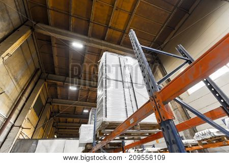 Big warehouse with packed ready goods on high shelves. View from below