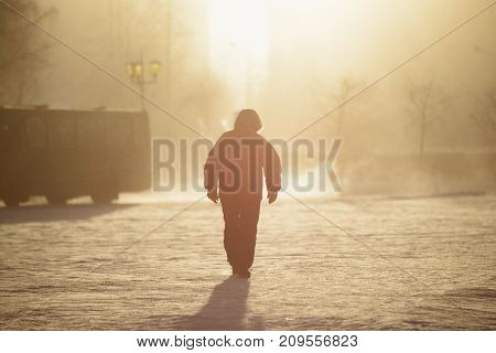 a lone man walking through a winter fog