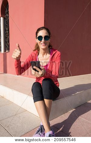Happy Woman Sitting With Phone And Thumb Up Sign