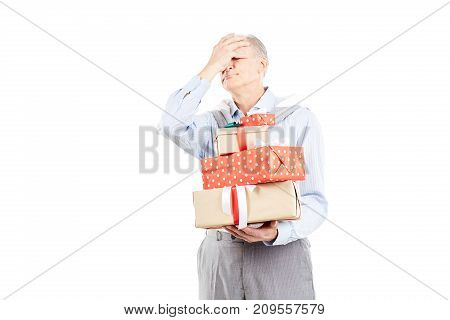Portrait of senior man holding heap of Christmas gifts