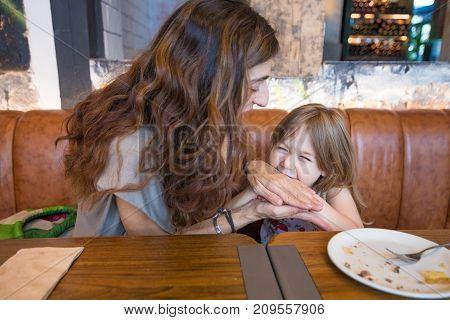 Little Girl Biting Her Mother Hand In Restaurant
