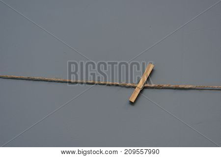A Single Wooden Clothes Pin On A Rope On Background Of A Gray Wall