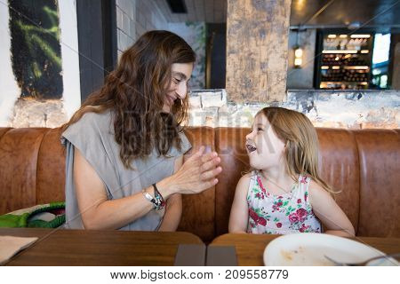 Little Girl Laughing With Mother Sitting In Restaurant