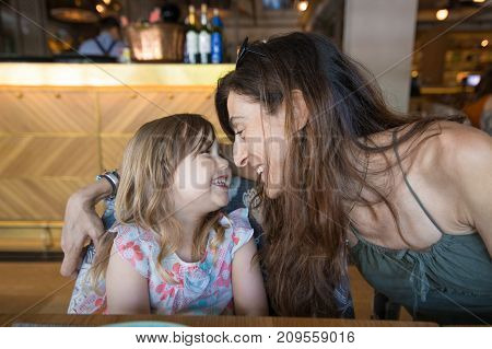 three years old blonde girl looking to woman mother laughing sitting in restaurant