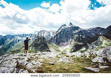 Lone hiker enjoying the view over the mountain summits in the alps.