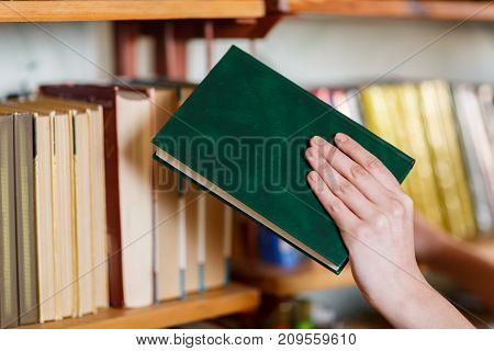 A woman's hand chooses a book in the library. Close-up . The concept of education.