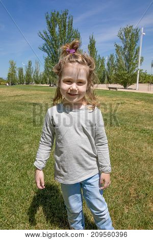funny portrait of blonde three years old child with pigtail grey shirt and blue jeans trousers standing in green grass in park and looking