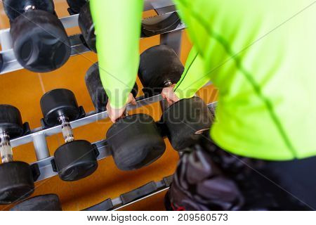 The hand of a strong man takes a heavy dumbbell in the gym. Close-up. The concept of sport.