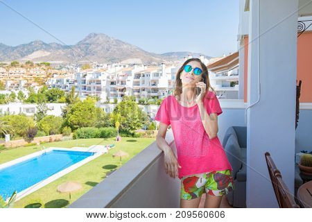 Smiling Woman Talking On Mobile In The Terrace Next To Pool