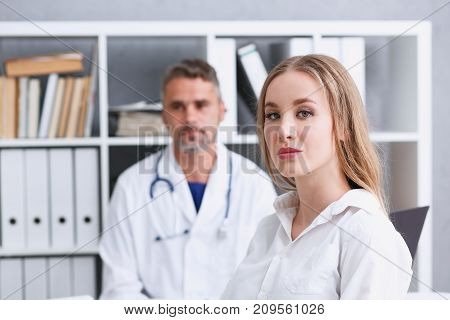 Satisfied happy beautiful smiling female with doctor at his office. High level and quality medical service therapeutist consultation appointment work and career physical healthy lifestyle concept
