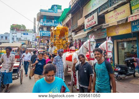 DELHI, INDIA - SEPTEMBER 25 2017: Unidentified people in the streets with a white plastic horse, very touristic atraction in the city of Paharganj, Delhi. Delhi is the 2nd most populous city in India after Mumbai.