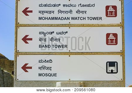 Hampi, India - November 20, 2012: Signpost for tourists with the pointer to Mohammadan Watch Tower Band Tower and Mosque in Hampi, Karnataka, India.