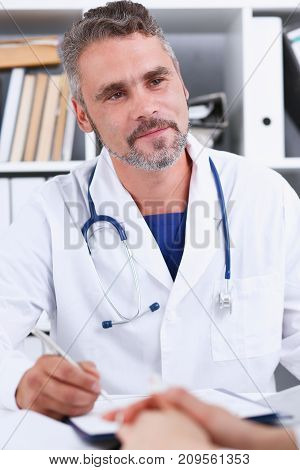 Smiling handsome mature doctor communicate with patient holding silver pen and pad. Physical agreement signature disease prevention consent sign 911 prescribe remedy healthy lifestyle concept