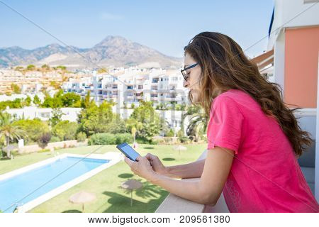 Woman Using Mobile In The Terrace Next To Pool