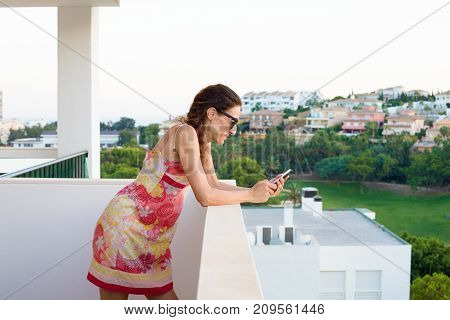 adult woman with red dress and sunglasses watching or using smartphone in the terrace. Behind green nature and houses