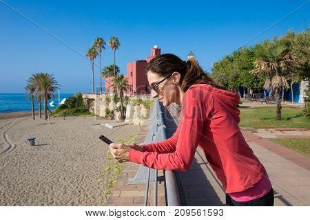 Woman Using Phone In Promenade Of Benalmadena
