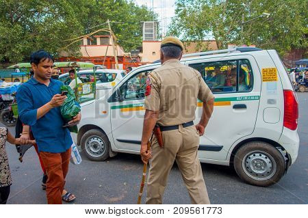 DELHI, INDIA - SEPTEMBER 25, 2017: A traffic policeman controling the traffic in Chandi Chowk area of the city. Traffic congestion is common in India's towns and cities.