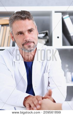 Friendly male doctor hold female arm in office during reception portrait. Examination result positive test calm down promise and cheer up grief and suffer treatment condolence ethics concept