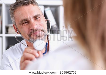 Handsome mature smiling male doctor hold in arm stethoscope head going to listen patient. Tool shop or store physical and disease prevention er consultant 911 pulse measure healthy lifestyle