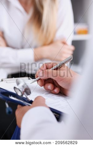 Male doctor arm hold silver pen filling patient complaints list clipped to pad. Physical exam er disease prevention ward round visitor check prescribe remedy healthy lifestyle concept