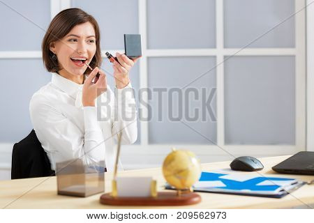 attractive business woman doing lip make-up at the office